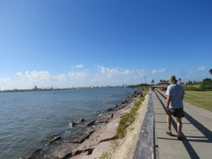 Walking down Surfside Jetty with an industrial complex on the horizon.