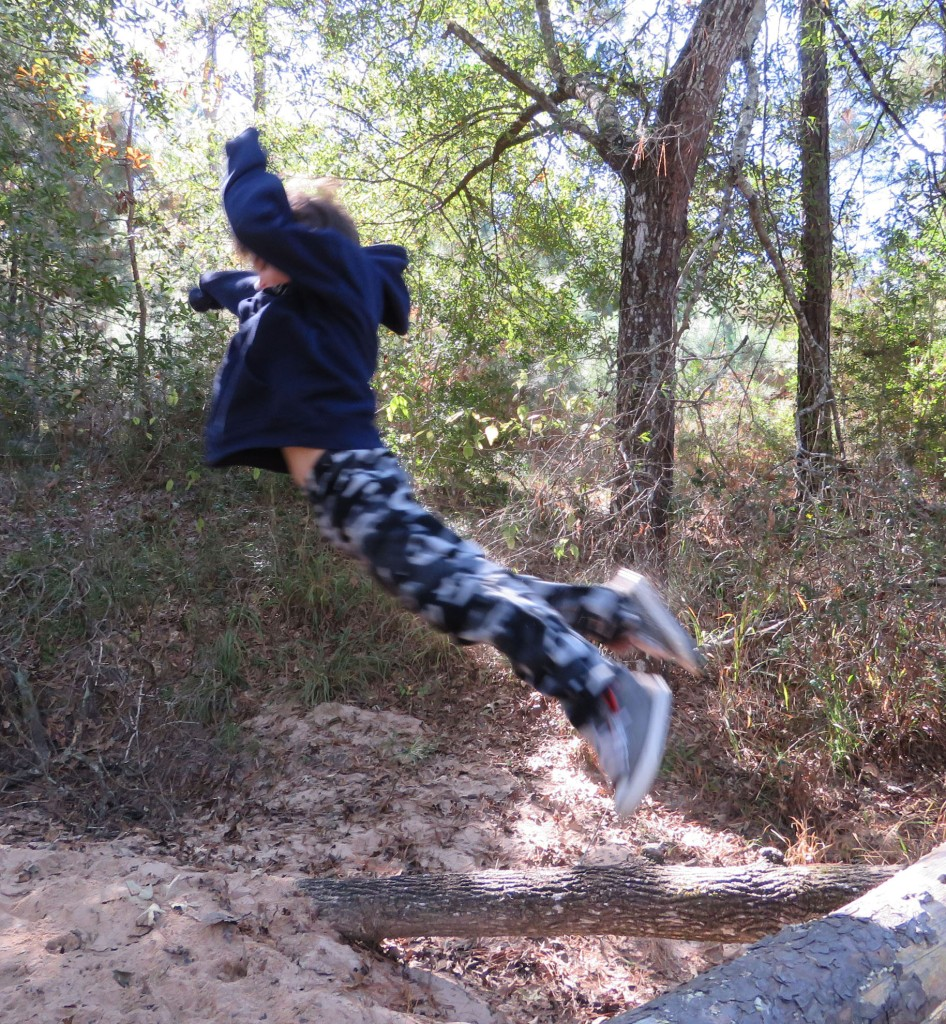 child leaping off a log